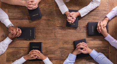 People's Praying Hands On Holy Bible